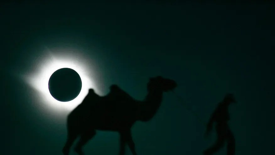 A man and his camel walk past as the sun is blocked by the moon during a solar eclipse in Gaotai, Gansu province August 1, 2008. REUTERS/Aly Song (CHINA) - RTR20JDU