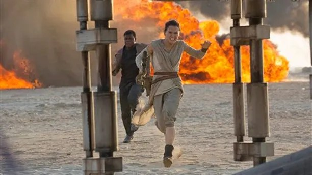 """This photo provided by Disney/Lucasfilm shows Daisy Ridley, right, as Rey, and John Boyega as Finn, in a scene from the film, """"Star Wars: The Force Awakens,"""" directed by J.J. Abrams. The movie opens in U.S. theaters on Friday, Dec. 18, 2015. (David James/Disney/Lucasfilm via AP)"""
