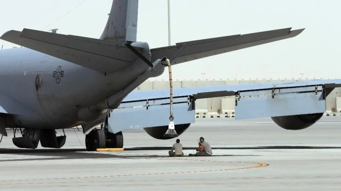 FILE -- In this photo taken Monday, March 9, 2015, U.S. technicians sit under the KC-135 refueling aircraft at the al-Udeid Air Base in Doha, Qatar.