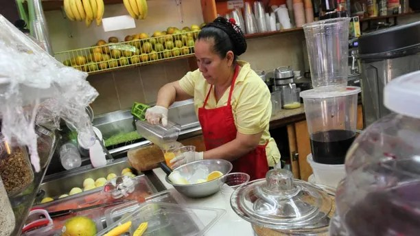Celina Alvarez, 51, works at Jugueria de regreso al Eden, her shop in the Queens borough of New York, Monday Aug. 3, 2015. As a campaign to raise the minimum wage as high as $15 has rolled to victory in such places as Seattle, Los Angeles and New York, it has bumped up against a harsh reality: Plenty of scofflaw businesses don't pay the legal minimum now and probably won't pay the new, higher wages either. (AP Photo/Tina Fineberg)