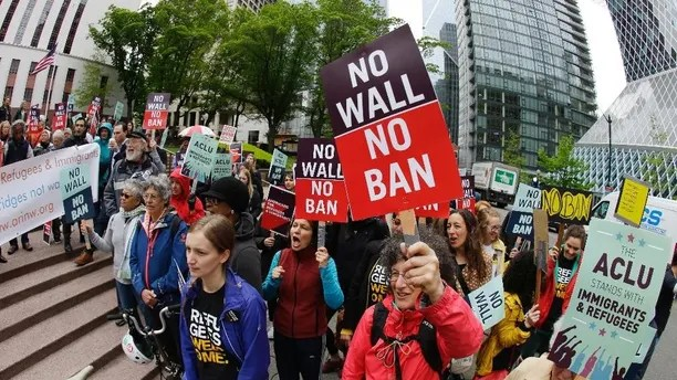 Protesters wave signs and chant during a demonstration against President Donald Trump's revised travel ban, Monday, May 15, 2017, outside a federal courthouse in Seattle. A three-judge panel of the 9th U.S. Circuit Court of Appeals heard arguments Monday in Seattle over Hawaii's lawsuit challenging the travel ban, which would suspend the nation's refugee program and temporarily bar new visas for citizens of Iran, Libya, Somalia, Sudan, Syria and Yemen. (AP Photo/Ted S. Warren)