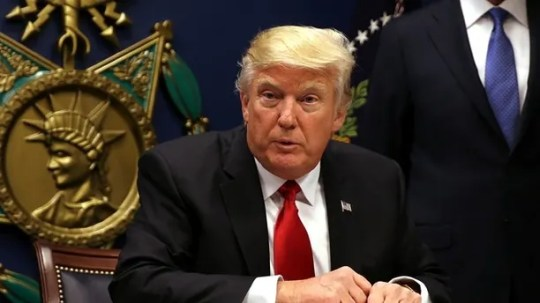 U.S. President Donald Trump signs an executive order to impose tighter vetting of travelers entering the United States, at the Pentagon in Washington, U.S., January 27, 2017. The executive order signed by Trump imposes a four-month travel ban on refugees entering the United States and a 90-day hold on travelers from Syria, Iran and five other Muslim-majority countries. Picture taken January 27, 2017. REUTERS/Carlos Barria - RTSXWM6