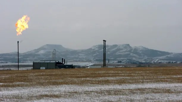 FILE - In this Feb. 25, 2015, file photo, a gas flare is seen at a natural gas processing facility near Williston, N.D. The Interior Department is moving to delay an Obama-era regulation aimed at restricting harmful methane emissions from oil and gas production on federal lands. (AP Photo/Matthew Brown)