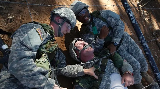 Private Sean Christopher Welliver (L) and Private John Hubbard (R) drag Private William Weaver (C), through an obstacle course as part of a first aid training exercise held during basic training at the Fort Sill Army Post in Fort Sill, Oklahoma November 5, 2009. REUTERS/Jessica Rinaldi (UNITED STATES MILITARY) - GM1E5B60N5H02