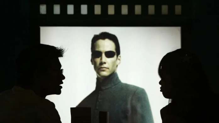 File photo: Chinese movie patrons wait in front of Hollywood star Keanu Reeves poster in the movie Matrix Reloaded showing at Paradise Warner Bros Cinema City in Shanghai July 18, 2003. (REUTERS/Claro Cortes IV)