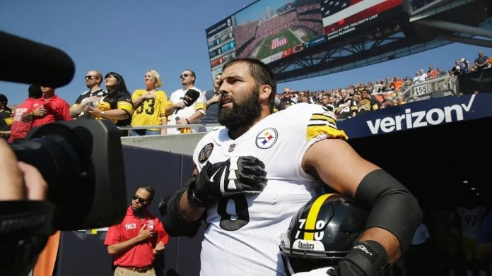 Pittsburgh Steelers offensive tackle and former Army Ranger Alejandro Villanueva stands outside the tunnel alone during the national anthem.