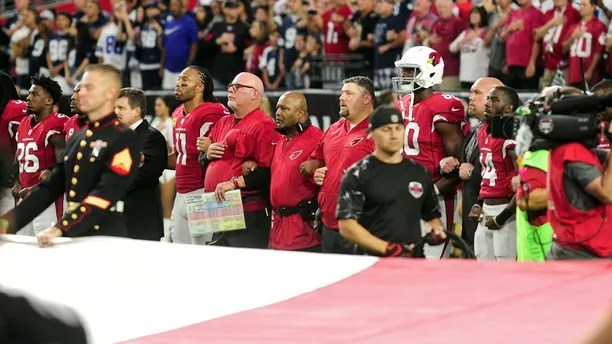 Sep 25, 2017; Glendale, AZ, USA; Arizona Cardinals wide receiver Larry Fitzgerald (11) , head coach Bruce Arians and teammates stand in front of a giant flag during the national anthem prior to the game against the Dallas Cowboys at University of Phoenix Stadium. Mandatory Credit: Matt Kartozian-USA TODAY Sports - 10308200