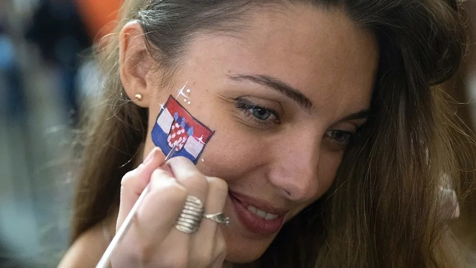A female soccer fan paints Croatia's flag on her face after Croatia beat England in the semifinal game on Wednesday in Moscow.