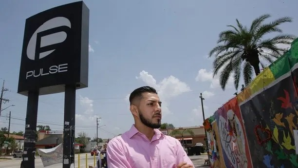 In this Tuesday, May 30, 2017 photo, Marco Quiroga, who works to support LGBTQ and social-justice causes in central Florida, reflects in front of one of the memorials at the Pulse Nightclub in Orlando, Fla. A year after the Pulse Nightclub shooting, the city's gay Latinos are trying to build up their community by forming support groups, seeking seats at the tables of power and creating a foundation to champion gays and Latinos. (AP Photo/John Raoux)