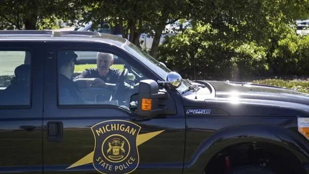 Michigan State Police talk outside Bishop International Airport, Wednesday morning, June 21, 2017, in Flint, Mich. Officials evacuated the airport Wednesday, where a witness said he saw an officer bleeding from his neck and a knife nearby on the ground.  On Twitter, Michigan State Police say the officer is in critical condition and the FBI was leading the investigation. (Shannon Millard/The Flint Journal-MLive.com via AP)