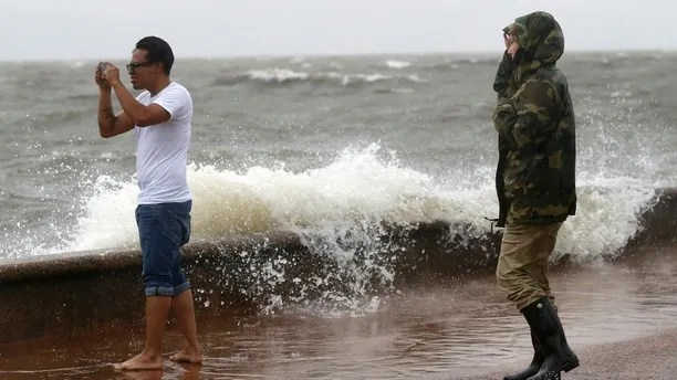 Julie Plaisance, right, and Renee Davila take photos on the shore of Lake Pontchartrain as weather from Tropical Storm Cindy, in the Gulf of Mexico, impacts the region in New Orleans, Tuesday, June 20, 2017. (AP Photo/Gerald Herbert)