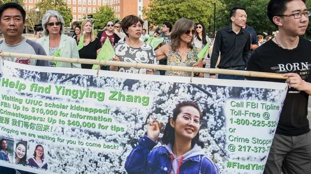 Yingying Zhang's father Ronggao Zhang, left, and her friend Xiaolin Hou carry the banner as community members join together to walk for Yingying, a Chinese scholar who went missing three weeks ago, Thursday, June 29, 2017, in Urbana, Ill. Illinois students and others from the wider community are gathering at the Urbana-Champaign campus to show support for the Chinese scholar who disappeared three weeks ago. (Holly Hart/The News-Gazette via AP)