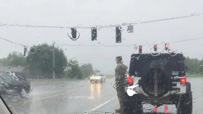 A soldier got out of his car to salute a funeral procession in the rain.