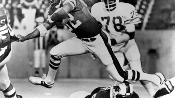 FILE - In this Sept. 3, 1977 file photo, Buffalo Bills' O.J. Simpson (32) runs past Tampa Bay Buccaneers' Council Rudolph (78) during an NFL football game in Buffalo, N.Y. Simpson, the former football star, TV pitchman and now Nevada prison inmate, will have a lot going for him when he appears before state parole board members Thursday, July 20, 2017, seeking his release after more than eight years for an ill-fated bid to retrieve sports memorabilia. (AP Photo, file)