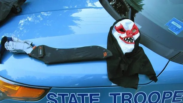 This Tuesday, July 25, 2017, photo released by the Maine State Police shows a clown mask and a machete that police said had been worn by Corey Berry, of Hollis, Maine. Police said Berry, 31, was arrested and charged with criminal threatening after they found him strolling down a street wearing the clown mask with the machete taped to his amputated arm. He was released after posting bail. (Maine State Police via AP)