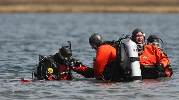 FILE- In this April 14, 2011 file photo, Suffolk County dive team police officers search for possible victims of a suspected serial killer in Hemlock Cove along Ocean Parkway near Cedar Beach, N.Y. On Tuesday, Sept. 12, 2017, Suffolk County Assistant District Attorney Robert Biancavilla said after the sentencing of Long Island carpenter John Bittrolff for the murder of two prostitutes in the early 1990s, that Bittrolff may be responsible for killing at least one of 10 victims whose remains have been found along a Long Island beach highway. (AP Photo/Robert Mecea, File)