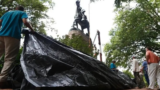 City workers prepare to drape a tarp over the statue of Confederate General Stonewall Jackson in Justice park in Charlottesville, Va., Wednesday, Aug. 23, 2017. The move intended to symbolize the city's mourning for a woman killed while protesting a white nationalist rally earlier this month. (AP Photo/Steve Helber)