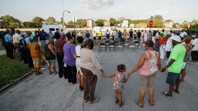 Chicago Police officers and community members gather in a prayer during a rally supporting efforts to stop violence in Chicago in July 2017.