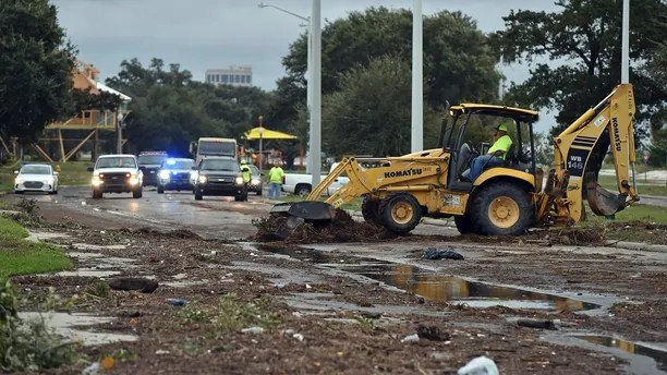 Biloxi public works employees clear debris from U.S. 90 in Biloxi Sunday, Oct. 8, 2017, after Hurricane Nate made landfall on the Gulf Coast.  (Justin Sellers/The Clarion-Ledger via AP)