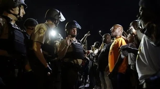 Officers and protesters face off along West Florissant Avenue, Monday, Aug. 10, 2015, in Ferguson, Mo. Ferguson was a community on edge again Monday, a day after a protest marking the anniversary of Michael Brown's death was punctuated with gunshots. (AP Photo/Jeff Roberson)