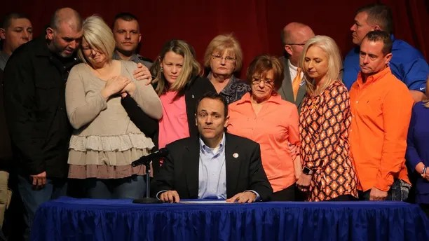 The parents of the late 15-year-old Bailey Holt, left, mourn while Kentucky Governor Matt Bevin signs the proclamation of the prayer on Friday, January. 26, 2018 in Benton, Kentucky. Marshall County High School reopened its doors Frida and as the school day began with an badembly. Police say two students were killed, 14 were injured by gunfire and another seven suffered other injuries when the boy opened fire at the school on Tuesday before the clbades began. (AP Photo / Robert Ray)