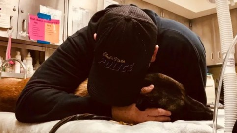 A Chula Vista police officer embraces Griffen, a 7-year-old Belgian Malinois, before the K9 officer passed away over the weekend.