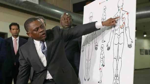 Pathologist, Dr. Bennet Omalu, gestures to a diagram showing where police shooting victim Stephon Clark was struck by bullets, during a news conference, Friday, March 30, 2018, in Sacramento, Calif. Omalu, who was hired by the family to conduct an independent autopsy, said Clark was shot seven times from behind and took up to 10 minutes to die. (AP Photo/Rich Pedroncelli)