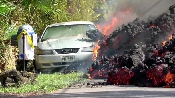Lava engulfs a Ford Mustang in Puna, Hawaii, U.S., May 6, 2018 in this still image obtained from social media video. WXCHASING via REUTERS ATTENTION EDITORS - THIS IMAGE WAS PROVIDED BY A THIRD PARTY. NO RESALES. NO ARCHIVES. MANDATORY CREDIT: WXCHASING. NO NEW USES AFTER JUNE 5, 2018. UNITED STATES OUT.     TPX IMAGES OF THE DAY - RC1F6FEBA420