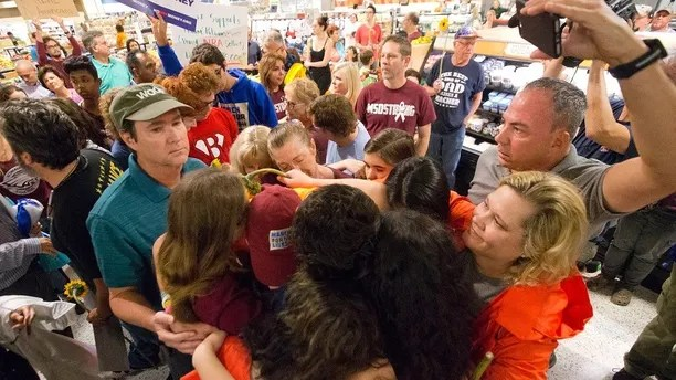 "Demonstrators do a group hug after a protest at a Publix Supermarket in Coral Springs, Fla., Friday, May 25, 2018. Students from the Florida high school where 17 people were shot and killed earlier this year did a ""die in"" protest at a supermarket chain that backs a gubernatorial candidate allied with the National Rifle Association. Shortly before the the ""die-in"" Publix announced that it will suspend political contributions. (AP Photo/Wilfredo Lee)"
