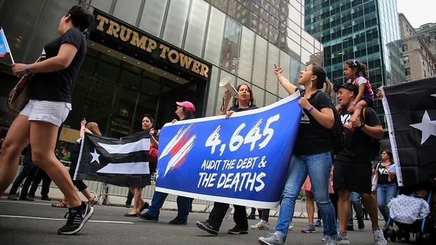 """Puerto Rico Day Parade participants turn their attention to Trump Tower as they march behind a banner in protest, marking """"4,645"""" deaths in the aftermath of hurricane Maria on the island and the Trump's administration emergency response, Sunday June 10, 2018, in New York. (AP Photo/Bebeto Matthews)"""