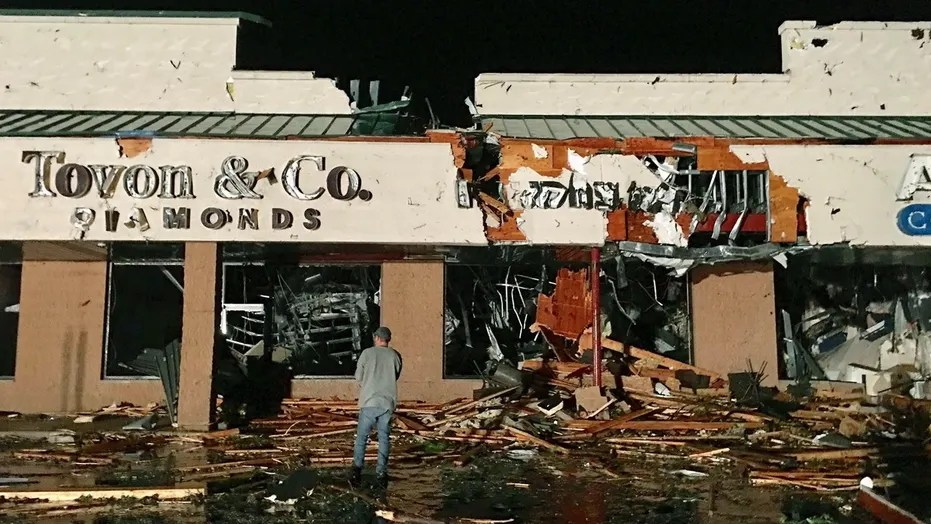 A bystander stands in front of several businesses in the area of the Wilkes Barre Township Commons after a tornado damaged several buildings and injured multiple people in Wilkes Barre Township, Pa.