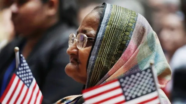 Hazera Khanom of Bangladesh listens during a naturalization ceremony, Tuesday, July 3, 2018, at the New York Public Library. Two hundred immigrants from 50 countries became citizens at the ceremony. (AP Photo/Mark Lennihan)