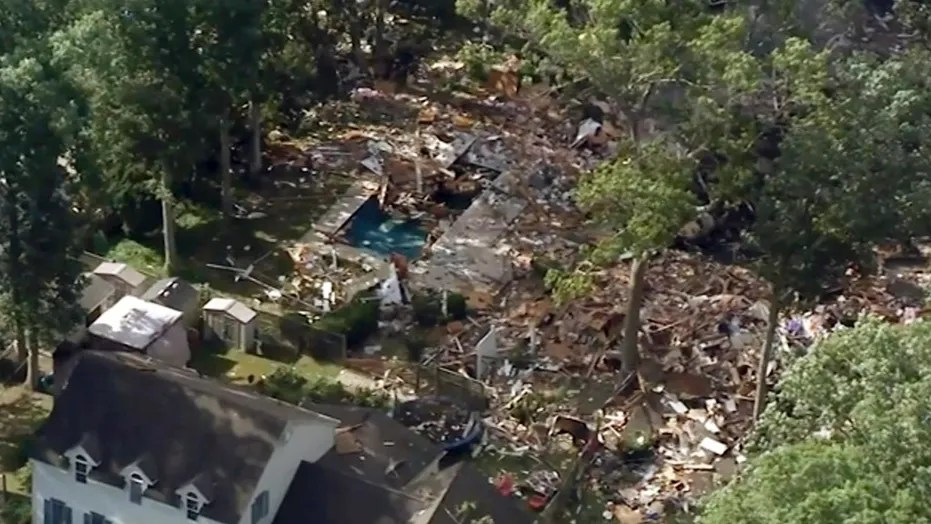 An image from video provided by WPVI shows debris covering the ground after a house exploded on Saturday in Newfield, N.J. Two people died.