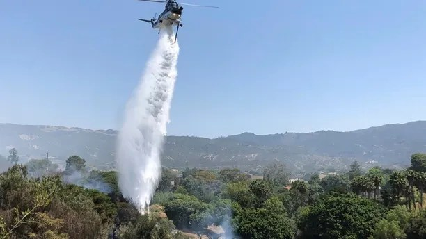 This Saturday, July 7, 2018, photo provided by the Santa Barbara County Fire Department shows a helicopter dropping water in concert with firefighters on the ground trying to extinguish stubborn smoldering areas of the fire off Fairview Ave., in Goleta, Calif. In heat-stricken Southern California, powerful winds that sent an overnight inferno hopscotching through the Santa Barbara County community of Goleta vanished in the morning, allowing firefighters to extinguish smoldering ruins of an estimated 20 structures, including homes. (Mike Eliason/Santa Barbara County Fire Department via AP)