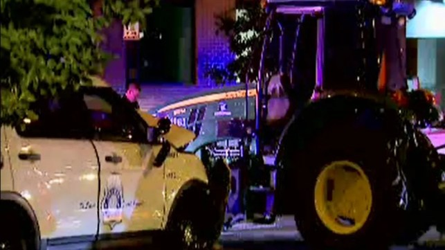 Two police officers were injured in a slow-speed chase with a John Deere tractor in downtown Denver on Friday night, police said.