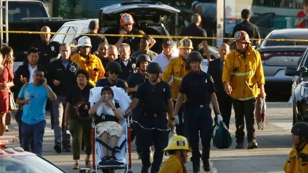 Los Angeles officials escort a woman being evacuated by emergency personnel after a gunman held hostages inside a Trader Joe's store in Los Angeles Saturday, July 21, 2018. Police believe a man involved in a standoff at the Los Angeles supermarket shot his grandmother and girlfriend and then fired at officers during a pursuit before he crashed into a utility pole outside the supermarket and ran inside the store. Hours after he took hostages in the store, the suspect surrendered. (AP Photo/Damian Dovarganes)