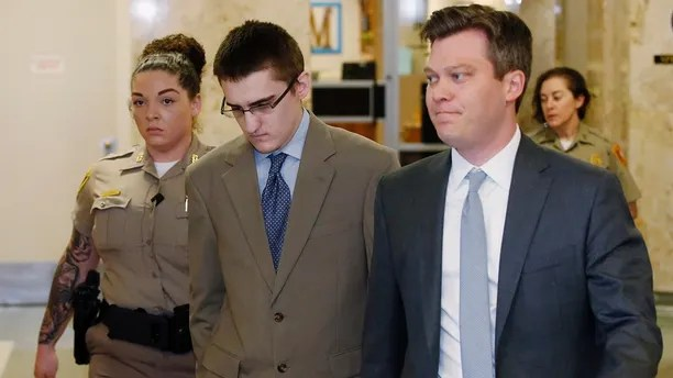 FILE - In this Tuesday, April 17, 2018 file photo, Michael Bever, center, is led from a courtroom following jury selection in his trial in Tulsa, Okla. At right is his defense attorney Corbin Brewster.  Bever, the younger of two brothers accused of fatally stabbing their parents and three siblings inside a suburban Oklahoma home, has been sentenced to life in prison but with the possibility of parole, Thursday, Aug. 9.  (AP Photo/Sue Ogrocki, File)