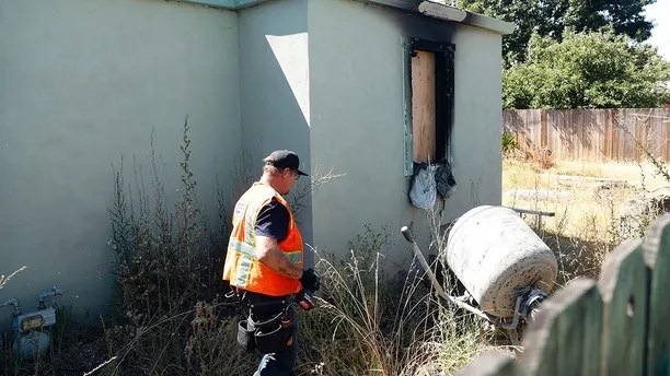 In this Aug. 5, 2018, picture, construction crews work at a house after a fire in Vallejo, Calif. Northern California police say a woman set herself on fire inside the home, killing herself and her twin 14-year-old daughters. (Scott Strazzante/San Francisco Chronicle via AP)