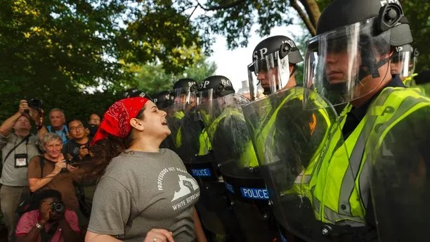 """Emily Filler attempts to dissuade state police from advancing on students rallying on the grounds of the University of Virginia on the anniversary of the """"Unite the Right"""" rally in Charlottesville, Va. Saturday, Aug. 11, 2018. The city of Charlottesville plans to mark Sunday's anniversary of a deadly gathering of white supremacists with a rally against racial hatred. (Craig Hudson/Charleston Gazette-Mail via AP)"""