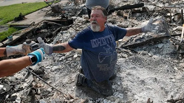 Rick Kincaid reacts as his wife Melodie Kincaid, left, finds his childhood toy as they sift through the charred remains of their home burned in the Carr Fire, Saturday, Aug. 11, 2018, in Redding, Calif. (AP Photo/John Locher)