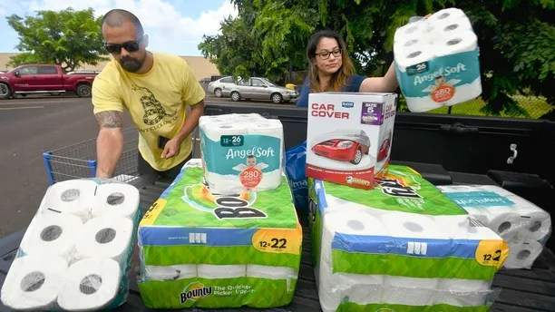 Bryce and Dom Boeder of Waimea, Kauai, load their truck with storm supplies in the parking lot of a Walmart store in Lihue, on the island of Kauai, Hawaii, Tuesday, Aug. 21, 2018. Hurricane Lane