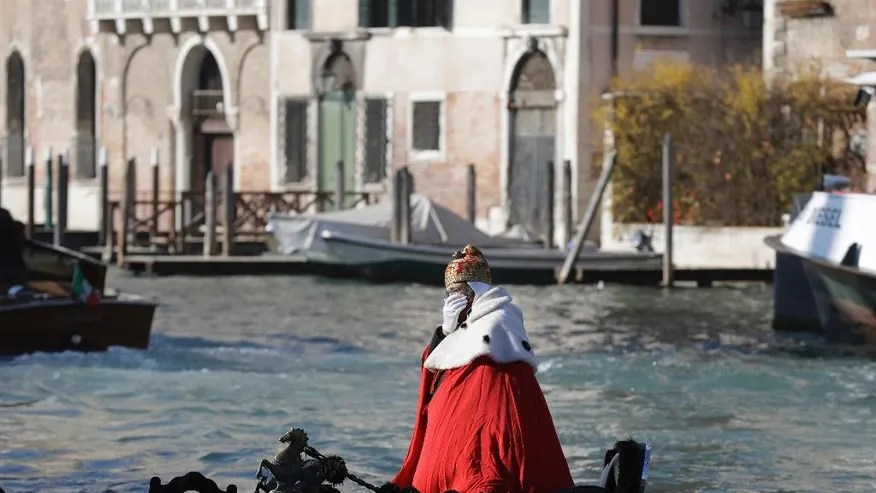 """A protester on a gondola impersonates the """"Doge of Venice"""" during a demonstration against the increasing number of tourists in Venice, Italy, Saturday, Nov.12. 2016. For decades, the number of Venetians have dwindled steadily and numerous factors are blamed _ high prices driven by a boom in tourism and the logistics of supplying a carless city and erosion by lapping waters among them. (AP Photo/Luca Bruno)"""