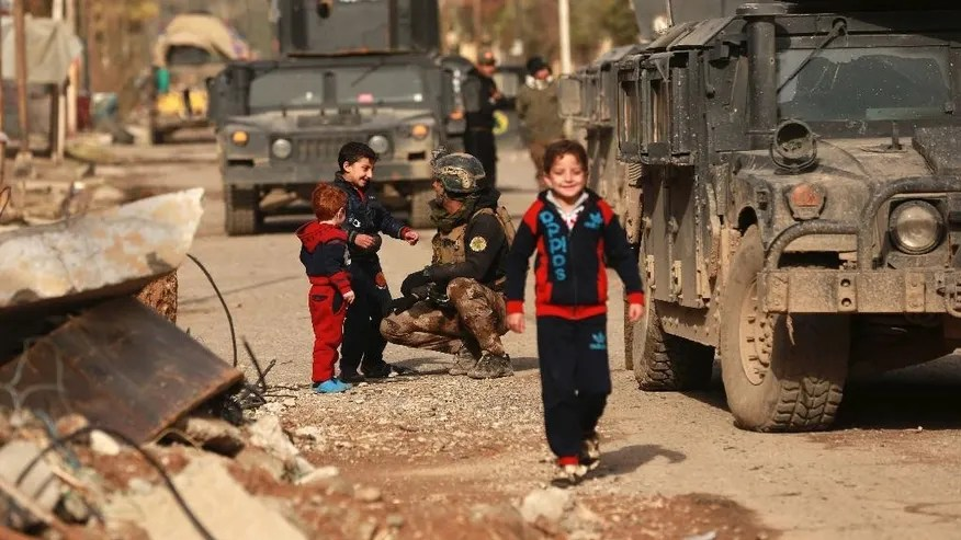Children welcome Iraqi special forces regaining control of Mishraq neighborhood from Islamic State militants in Mosul, Iraq, Friday, Dec. 16, 2016. (AP Photo/Hadi Mizban)