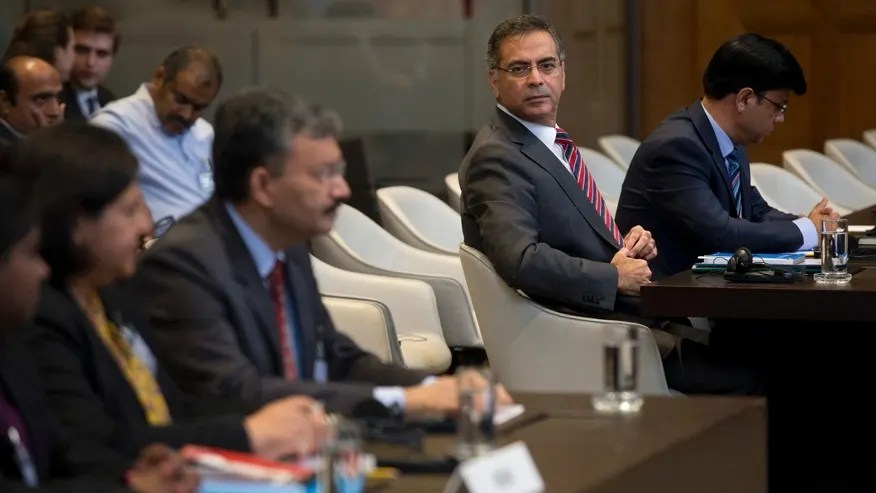 Moazzam Ahmad Khan, head of Pakistan's delegation and ambassador, second right, and Dr. Deepak Mittal, joint secretary of India's Ministry of External Affairs, front row third from left, wait for judges to enter and read the World Court's verdict in The Hague, Netherlands, Thursday, May 18, 2017. India took Pakistan to the United Nations' highest court in an attempt to save the life of an Indian naval officer sentenced to death last month by a Pakistani military court after being convicted of espionage. (AP Photo/Peter Dejong)