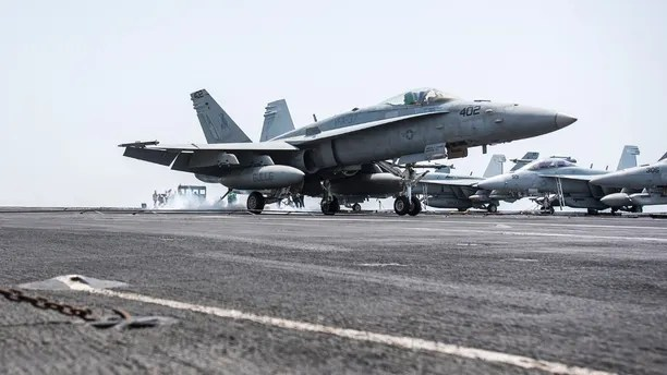 """170411-N-YL257-028 ARABIAN GULF (April 11, 2017) An F/A-18C Hornet attached to the """"Ragin' Bulls"""" of Strike Fighter Squadron (VFA) 37 lands on the flight deck of the aircraft carrier USS George H.W. Bush (CVN 77) (GHWB). GHWB is deployed in the U.S. 5th Fleet area of operations in support of maritime security operations designed to reassure allies and partners, and preserve the freedom of navigation and the free flow of commerce in the region. (U.S. Navy photo by Mass Communication Specialist 3rd Class Christopher Gaines/Released)"""
