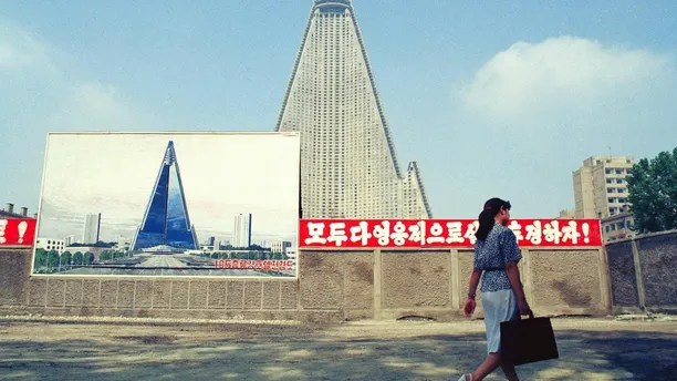"""FILE - In this Aug. 22, 1990, file photo, a woman walks past the site of the Ryugyong Hotel under construction in Pyongyang, North Korea. Sign in red reads """"Let's all together struggle heroically!"""" Walls set up to keep people out of a construction area around the gargantuan Ryugyong Hotel were pulled down in July 2017 as the North marked the anniversary of the Korean War armistice to reveal two broad new walkways leading to the building and the big red propaganda sign declaring that North Korea is a leading rocket power. (AP Photo/Vincent Yu, File)"""