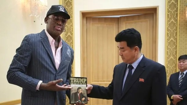 """In this June 15, 2017, file photo, former NBA basketball star Dennis Rodman presents a book titled """"Trump The Art of the Deal"""" to North Korea's Sports Minister Kim Il Guk Thursday, June 15, 2017, in Pyongyang, North Korea. (AP Photo/Kim Kwang Hyon, File)"""