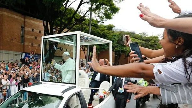 People wave to Pope Francis as he passes by in his popemobile in Medellin, Colombia, Saturday, Sept. 9, 2017. Francis flew to a rain-soaked Medellin on Saturday to console orphans, the poor and sick — and to demand priests and ordinary Colombians look beyond rigid church doctrine to care for sinners and welcome them in. (AP Photo/Fernando Vergara)