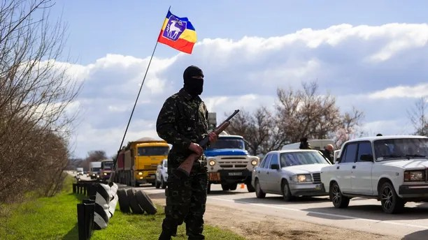 An armed member of a local self-defense unit mans a checkpoint on the highway between Simferopol and Sevastopol in the Crimean peninsular March 13, 2014. Serbian paramilitaries have offered their help to pro-Russian self-defence volunteers who set up road blocks on the main road to the Crimean port city of Sevastopol, home to the Russian Black Sea fleet. Road blocks were set up last week when pro-Russian men in green uniforms without insignia started appearing outside bases taking control of naval and military installations in Crimea. REUTERS/Thomas Peter (UKRAINE  - Tags: CIVIL UNREST MILITARY POLITICS) - GM1EA3E00B401