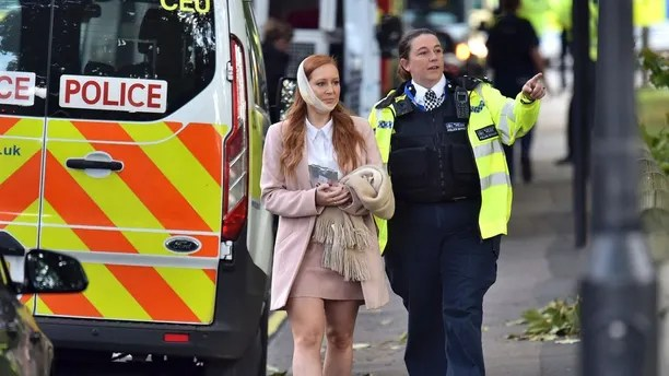 An injured woman is assisted by a police officer close to Parsons Green station in west London after an explosion on a packed London Underground train, Friday, Sept. 15, 2017. London's Metropolitan Police says a fire on the London subway has been declared a